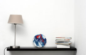 Red and Blue Art on Shelf With Lamp and Books