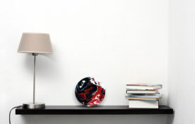 Red and Black Art on Shelf with Lamp and Books